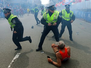 Bill Iffrig, 78, lies on the ground as police officers react to a second explosion at the finish line of the Boston Marathon in Boston.