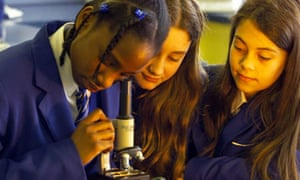 Pupils look down a microscope in a science lesson