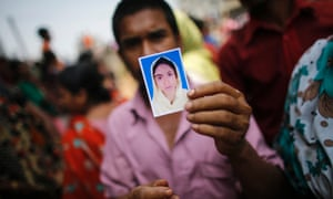 A relative holds a picture of a missing worker, who was working in the Rana Plaza building when it collapsed, in Savar.
