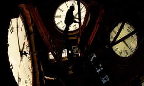 Man's shadow on three clock faces