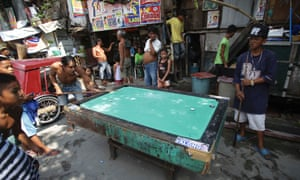 Playing pool is a popular pastime among many Filipinos. Here people from a poor district of Manila play using wooden discs.