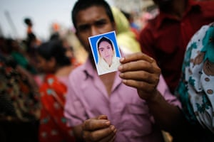 Building collapse: A relative holds a picture of a missing garment worker