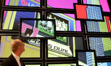 a man watches a wall of video screens