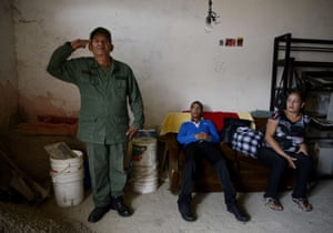 Miguel Guevara, 73, a member of the Venezuelan Militia, salutes watched by his wife and grandson, at his home in Catia, a poor neighbourhood in west Caracas. Guevara is one of the 130,000 men and women of the Militia, created by the late President Hugo Chavez, who says he will continue defending Chavez's revolution with his life.
