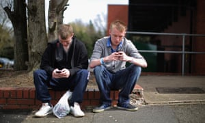 Two youths send text messages on their smart phones in Corby.