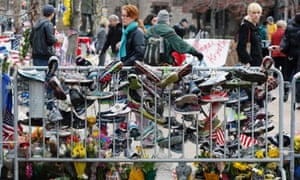 Running shoes hang from a barrier at a makeshift memorial in Copley Square in Boston. Businesses opened and traffic was allowed to flow all the way down Boylston Street on Wednesday morning for the first time since two explosions at the Boston Marathon.