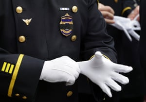 An Arlington, Massachusetts police officer dons white gloves as he prepares to enter the memorial service.