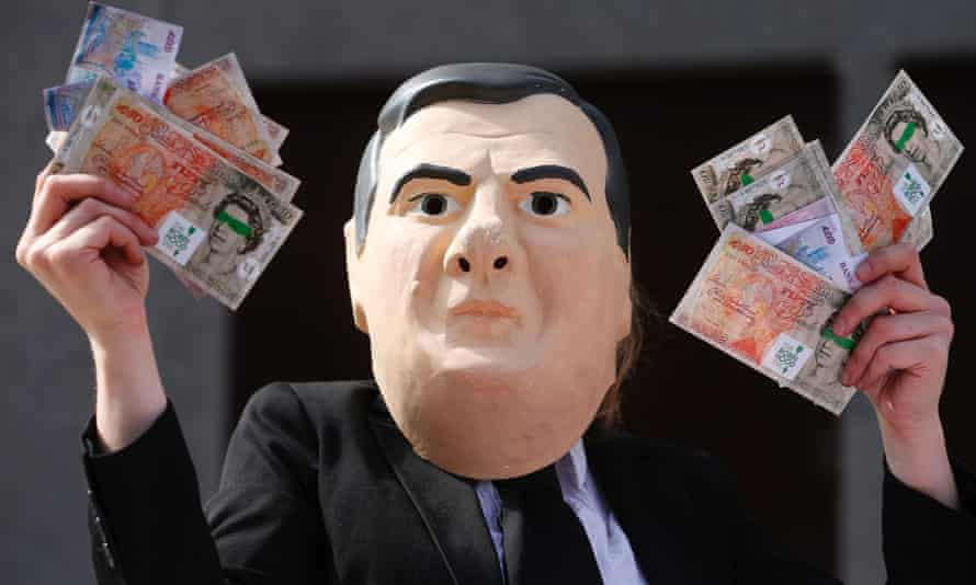 A Robin Hood Tax demonstrator wearing a George Osborne mask outside the Barclays AGM at the Royal Festival Hall in London.