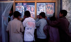 A group of boys watch a Bollywood film through the window of a video rental shop Kabul, Afghanistan