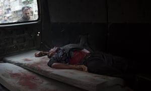 A Syrian man looks at the body of a man lying in a truck outside a hospital in the northern city of Aleppo in October 2012. The photographer, Fabio Bucciarelli, was awarded the 2013 Robert Capa Gold Medal for demonstrating 'exceptional courage' in capturing images of the conflict in Syria.