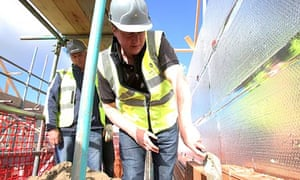 David Cameron lays bricks during a visit to a building site in Lancashire