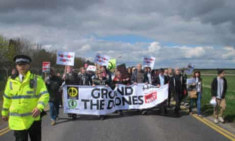 Protesters march to the perimeter fence of RAF Waddington, Lincolnshire