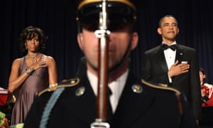 President Barack Obama and first lady Michelle Obama stand behind an honour guard soldier during the playing of national anthems at the 2011 White House correspondents' dinner.