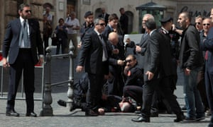 A Carabiniere police officer lies on the ground after being shot outside the Chigi Premier's office on April 28, 2013 in Rome, Italy. Two military police officers were shot in the square outside Palazzo Chigi while the new government of Enrico Letta was being sworn in.