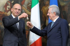 Premier Enrico Letta, left, takes the cabinet minister bell handed over by former Premier Mario Monti during the handover ceremony.
