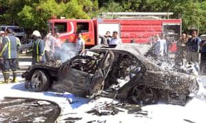 叙利亚消防员和警察在据称针对大马士革叙利亚总理瓦尔哈尔基的炸弹爆炸事件后检查了一辆烧毁的汽车。