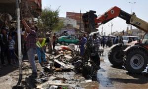 在巴格达以南的Diwaniya省发生汽车炸弹爆炸后,街道清洁工拆除了路面上的碎片。