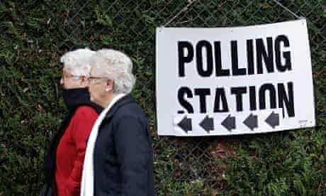 Women pass a polling station sign during the London mayoral and assembly elections in London