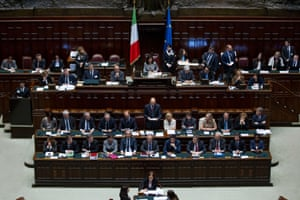 Prime Minister Enrico Letta, standing at center surrounded by his Cabinet, delivers his speech during a vote of confidence to confirm the government, in the lower house of Parliament, in Rome, Monday, April 29, 2013.
