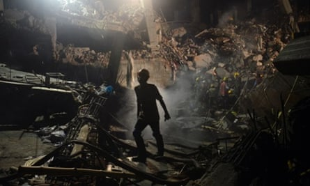 A worker leaves the site where a garment factory building collapsed near Dhaka, Bangladesh, killing at least 381 people. Rescuers have given up hopes of finding any more survivors in the remains of a building that collapsed five days ago.