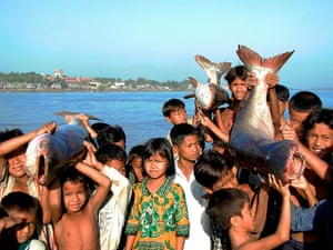 Greater Mekong: Crowd of children with Pra or River catfish, Cambodia (Kampuchea)