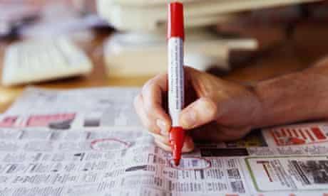 A man circling ads in newspaper