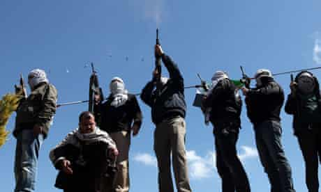 Masked gunmen supporting the Fatah movement fire automatic weapons in the air at West Bank funeral