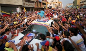 Pretty popular: Opposition presidential candidate Henrique Capriles, in the blue shirt, shakes hands with supporters while riding on top of a vehicle during a campaign rally in Maracay, Venezuela, last night.
