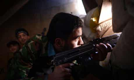 A Syrian rebel observes regime forces in Aleppo