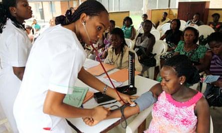 A nurse checks a pregnant woman's blood pressure at a maternity hospital in Nigeria.