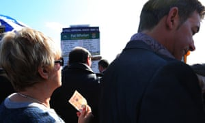 A racegoer waits to make a bet at Aintree.