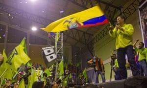 Ecuadorean president Rafael Correa waves the national flag during a political rally in Alausi