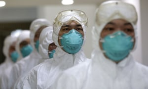 Medical workers dressed in protective clothing take part in an avian flu drill in Wuhan city, Hubei province, China.  A strain of bird flu that has been found in humans for the first time in eastern China is not a cause for panic, the World Health Organization has said, as the number of people infected rose to 21, with six deaths.