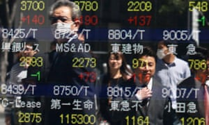 Pedestrians look at stock market indexes on a public display board in Tokyo, Japan. Japanese stocks soared today on a weaker Yen and a report that the Bank of Japan would start to buy government bonds this week.