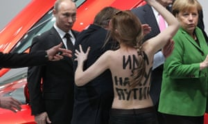 Another scene from Hannover: President Putin is confronted by an activist of the Ukrainian women rights group Femen as Angela Merkel looks on during their visit to an industrial exhibition.