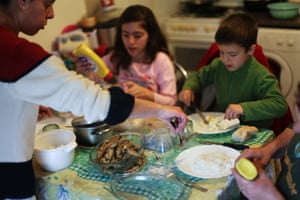 Elena Baptista, left, serves a meal to her daughter Vania, 12, left, son Joao, 7, and husband Pedro, partially seen on the right, in their house's kitchen/living room in Loures, outside Lisbon.