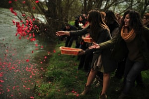 Female Roma people throw flower petals into the Arga River in honor of their ancestors on the International Roma Day in Pamplona northern Spain.