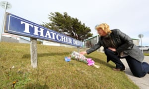 A Falkland resident places a little Union Flag and a bunch of flowers on the lawn to honour the memory of former British PM Margaret Thatcher, in Port Stanley, Falkland Islands. Photograph: Tony Charter/AFP/Getty Images