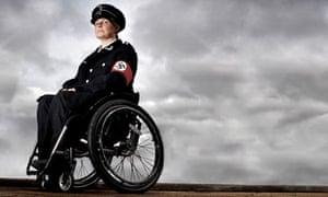 Liz Crow in a wheelchair wearing a Nazi uniform