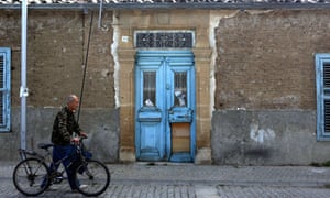 A Cypriot man walks with his bicycle past a derelict house