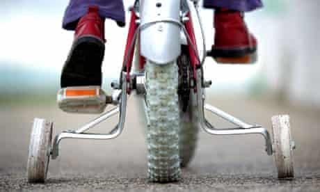 Young child on a bicycle with stabilisers