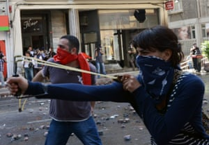A demonstrator uses a slingshot as clashes erupt between police and protesters during May Day celebrations in Istanbul, Turkey, Wednesday May 1, 2013.