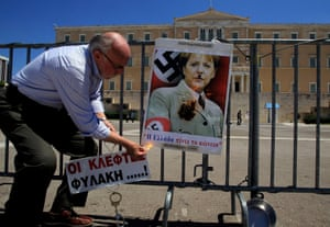 A pensioner burns a poster showing German Chancellor Angela Merkel dressed in a Nazi uniform in front of the Greek Parliament during a rally marking May Day in central Athens, Greece, 01 May 2013.