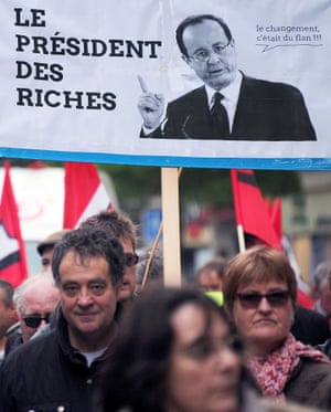 """A demonstrator holds a board which reads : """"The president of the rich, the change, it was a blank"""", referring to French president, during the workers parade as part of the  May Day rallies on May 1, 2013 in Strasbourg, eastern France"""