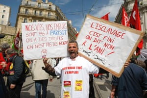 """A worker holds placards reading """"Slavery is Over, We Say No to the ANI (Government labor reform) - Our Lives, Our jobs are not at Parisot (head of union bosses), We Have Rights, We are not Idiots!"""" during May Day celebrations, in Marseille, France, Wednesday May 1, 2013."""