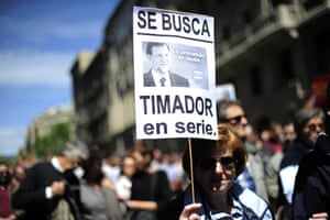 """A woman holds a placard depicting Spanish Prime Minister Mariano Rajoy and reading """"wanted, serial swindler"""" during a Labour Day march in the centre of Barcelona on May 1, 2013."""