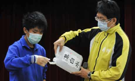 A teacher guides a student on how to use disinfectant in a school in Taipei - H7N9 bird flu