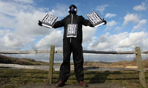 A masked man protesting against fracking
