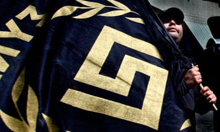 A member of Golden Dawn holds a flag bearing the party's logo
