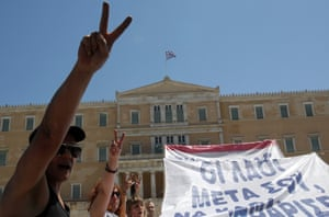 Protesters shout slogans and hold banners in front of the House of Parliament in Athens.